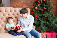 Portrait of father and adorable son holding bauble against domestic festive backdrop with Christmas tree Stock Images