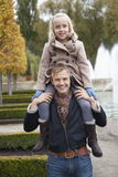 Portrait of father carrying daughter on his shoulders at park Stock Images