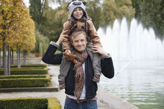 Portrait of father carrying son on his shoulders at park Royalty Free Stock Photo