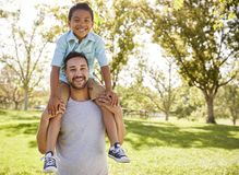Portrait Of Father Carrying Son On Shoulders In Park stock image