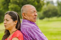 Portrait of father and daughter back to back each other at outdoors, in the park stock image