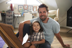 Portrait Of Father And Daughter With Chalkboard In Playroom Stock Photography