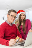 Portrait of father and daughter shopping online during Christmas royalty free stock photography