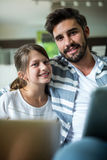 Portrait of father and daughter using laptop and digital tablet in the living room Stock Photos