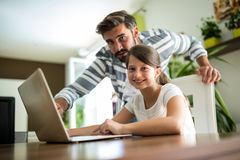 Portrait of father and daughter using laptop in the living room Royalty Free Stock Photos
