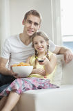 Portrait of father and daughter watching TV with bowl full of wheel shape snack pellets Stock Images