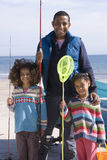 Portrait of father with daughters holding fishing nets on beach stock images