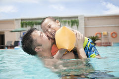 Portrait of father embracing his smiling son in the pool Royalty Free Stock Images