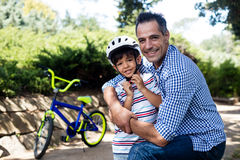Portrait of father embracing his son in park. On a sunny day royalty free stock photo