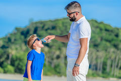 Portrait of father giving water to his thirsty handsome boy on the desert tropical beach. Portrait of father giving water to his thirsty handsome boy on the Royalty Free Stock Photo