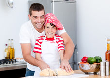 Portrait of a father and his son preparing a meal. In a kitchen Stock Photos