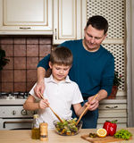 Portrait of a father and his son preparing a salad in the kitchen Stock Images