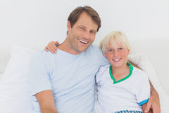 Portrait of a father and his son. Sitting on the bed Stock Image