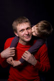 Portrait of a father with his son. Six-year boy hugging his father against a black background in the studio Royalty Free Stock Photos