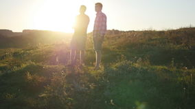 Portrait of father with his son talking outdoor at sunset. Two adult men are standing on green grass on the hill and. Speaking with each other. Father and son stock video footage