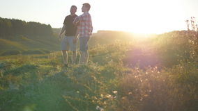 Portrait of father with his son talking outdoor at sunset. Two adult men are standing on green grass on the hill and. Speaking with each other. Father and son stock video