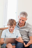 Portrait of a father and his son using a tablet computer. In a living room Royalty Free Stock Photo
