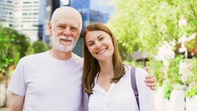 Portrait of father and his young daughter standing on street. Happy family enjoying time together stock footage