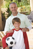 Portrait of a father with his young son, holding a football Royalty Free Stock Image