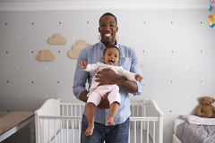 Portrait Of Father Holding Baby Daughter In Nursery Stock Images