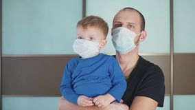 Portrait of Father holding Cute little toddler baby boy child wearing protective medical mask, Dad and son standing in stock video
