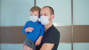 Portrait of Father holding Cute little toddler baby boy child wearing protective medical mask, Dad and son standing in stock video footage