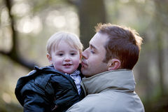 Portrait of a father holding his son in the park, smiling stock photo