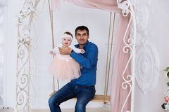 A portrait of the father is holding a smart little girl who smiles and poses in a beautiful fluffy gown of tender color. A men in a blue shirt is playing with Stock Images