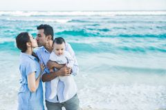 Father kissing mother while holding their cute son. Portrait of father kissing mother while holding their cute son at the beach with copy space stock image