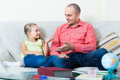 Portrait of father and little girl discussing something  indoors Royalty Free Stock Photo