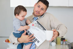 Portrait of father multi tasking in house Stock Image