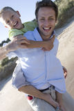Portrait of father piggybacking son on beach royalty free stock photos