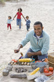 Portrait of father preparing barbecue on beach, family running in background Stock Image