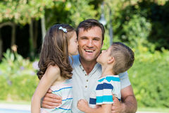 Portrait of father receiving kisses from son and daughter. In the park Stock Image