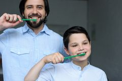 portrait of father and son brushing teeth together stock photography