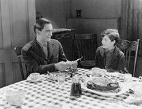 Portrait of father and son at dinner table stock photos