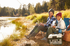 Portrait Of Father And Son Fishing By Lake Stock Images