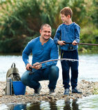 Portrait of father and son fishing with rods. Portrait of happy glad smiling father and son fishing with rods in summer day Stock Photos