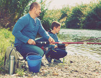 Portrait of father and son fishing with rods Royalty Free Stock Photos