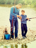 Portrait of father and son fishing with rods. Portrait of  smiling father and  son fishing with rods in summer day Stock Images