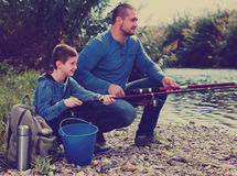 Portrait of father and son fishing with rods Stock Photos