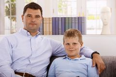Portrait of father and son at home. Portrait of father and son sitting on sofa at home, looking at camera royalty free stock image