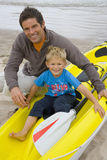 Portrait of father and son with kayak on beach Royalty Free Stock Photo