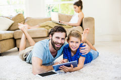 Portrait of father and son lying on rug and using digital tablet Royalty Free Stock Photography