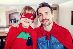 Portrait of father and son pretending to be superhero in living room Stock Image
