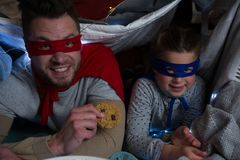 Portrait of father and son pretending to be superhero. While eating cookies Stock Photo