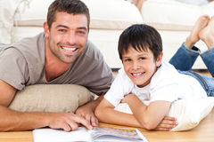 Portrait of a father and son reading a book. Together on the floor at home Royalty Free Stock Images