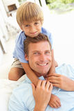 Portrait Of Father And Son Relaxing On Sofa Royalty Free Stock Image