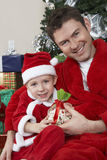 Portrait Of Father And Son In Santa Claus Outfit Holding Present Royalty Free Stock Photos