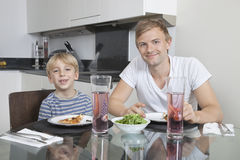 Portrait of father and son smiling at breakfast table Stock Photo